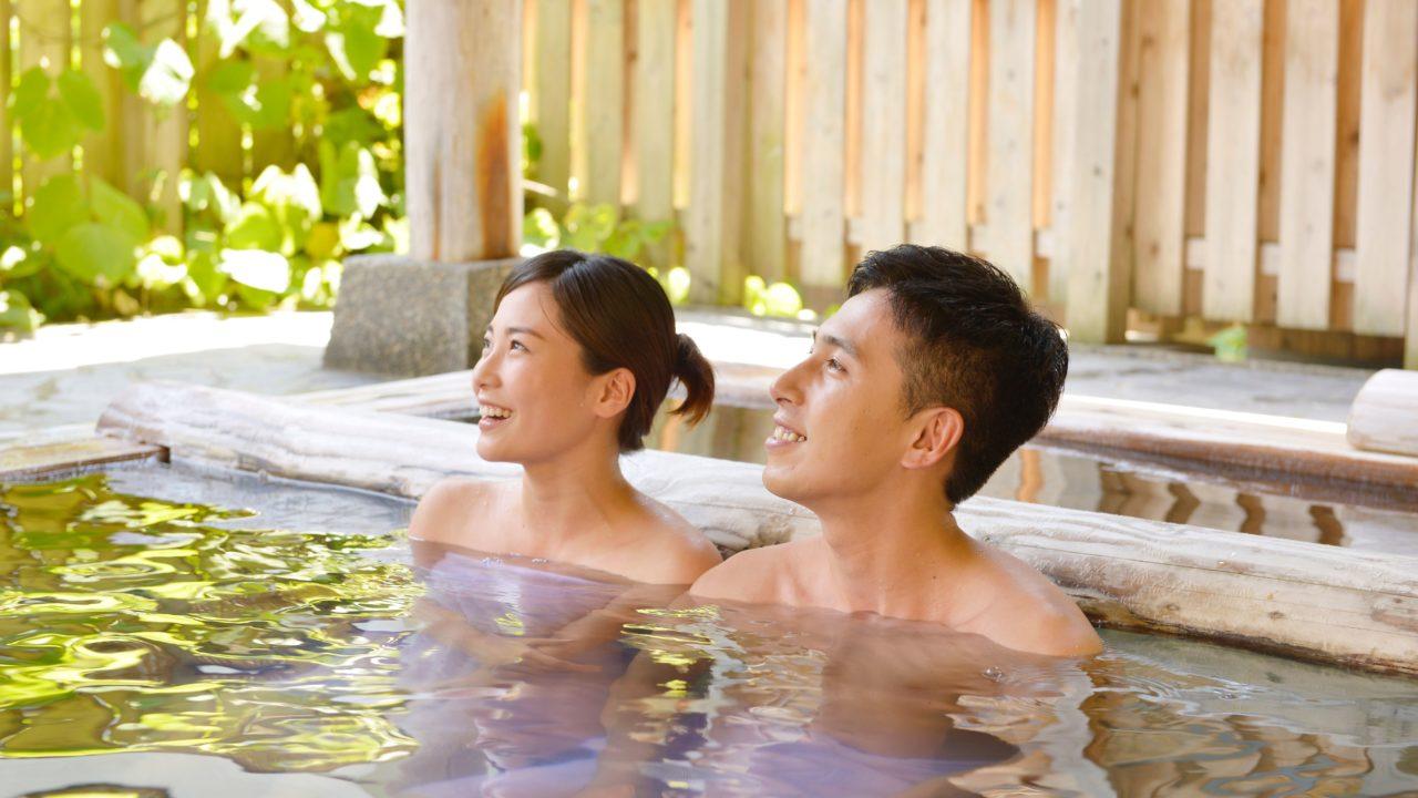 温泉につかるカップル