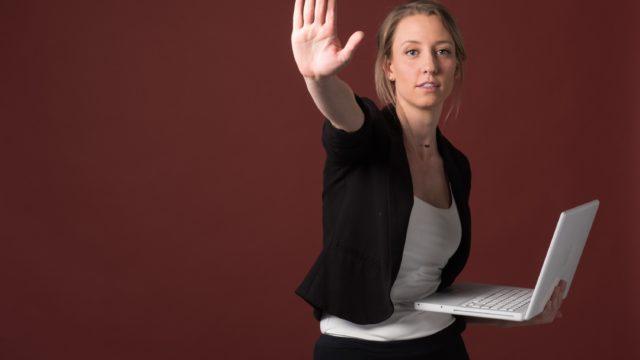 パソコン片手に手を上げている外国人女性