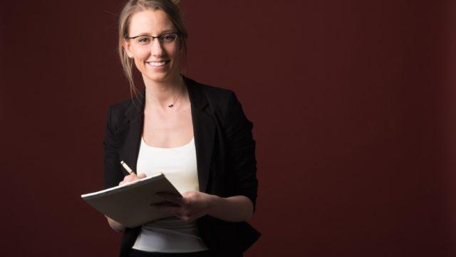 ノートとペンを手に持ってメモをする外国人女性