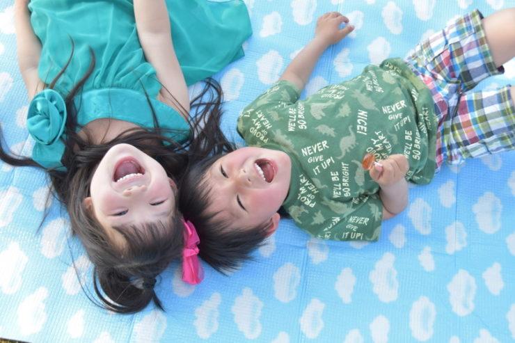 床に寝転んで笑う子供の兄弟