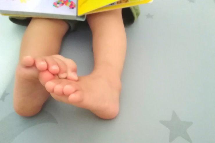 絵本を読んでいる子供の足
